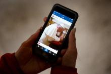 """ILLUSTRATION - Ein Frau hält am 19.03.2016 in Dresden (Sachsen) ein Smartphone mit dem Instagram-Account von Papst Franziskus in den Händen. Der Papst wird künftig unter """"Franciscus"""", der lateinischen Form seines Namens, Fotos und kurze Videos auf der Foto-Plattform mit Nutzern in aller Welt teilen. Foto: Arno Burgi/dpa (zu dpa """"Der Papst ist jetzt bei Instagram"""" vom 19.03.2016) +++(c) dpa - Bildfunk+++"""